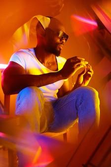 Классно. кинематографический портрет стильного молодого человека в неоновой освещенной комнате. яркие неоновые цвета. афро-американская модель, музыкант в помещении. молодежная культура в партии, фестивальном стиле и музыкальной концепции.
