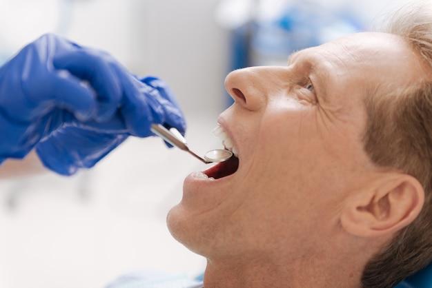 그는 치과 거울을 사용하여 환자의 치아를 확인하는 동안 의사 사무실에 앉아 품위있는 멋진 용기있는 사람