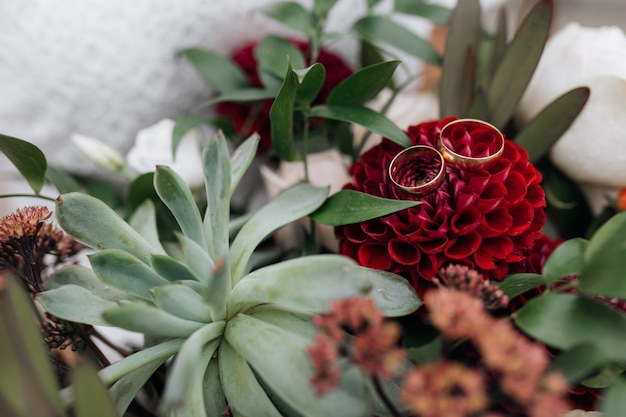 Classy golden wedding rings lie on the red flower in bride's bouquet