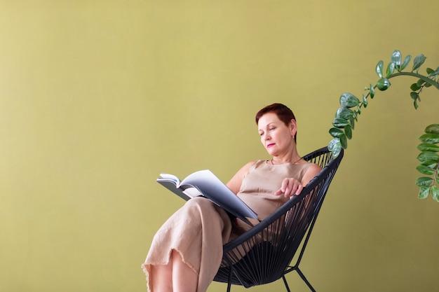 Classy mature woman reading a magazine