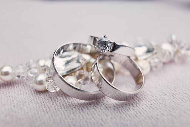 화이트 골드 소재의 고급 실버 결혼 반지가 크리스탈 브레이슬릿에 놓여 있습니다.