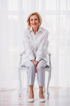 Classy woman sitting on chair while looking at the camera