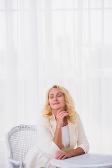 Classy woman with closed eyes sitting on chair
