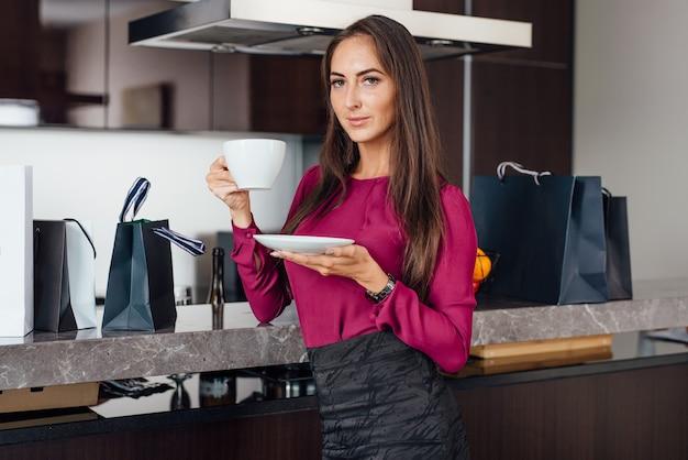 買い物の後にリラックスしてキッチンに立ってコーヒーを飲む上品な若いラテン女性。
