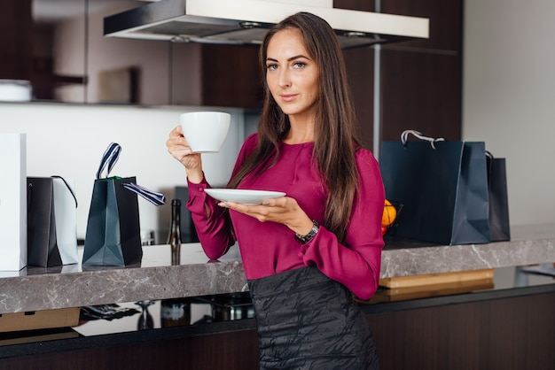 Classy young latin woman drinking coffee standing in the kitchen relaxing after shopping.