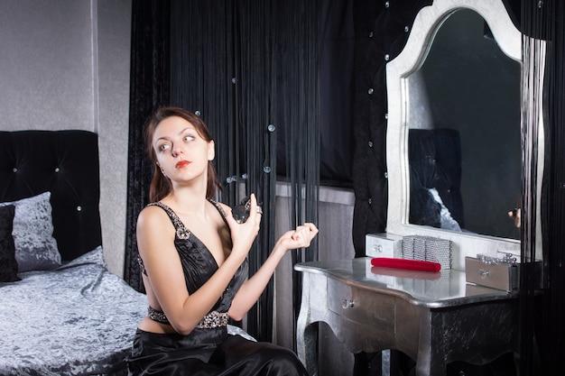 デートの準備中に香水をスプレーする黒いドレスを着た上品な若い女性。