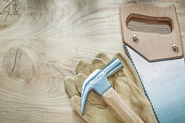 Claw hammer leather safety gloves stainless hacksaw on wooden board construction concept