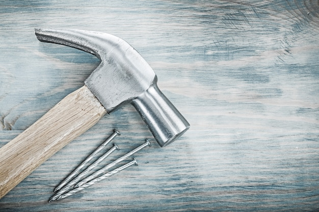 Claw hammer metal nails on wooden board construction concept