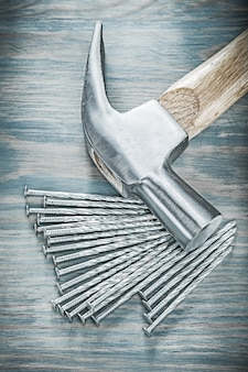 Claw hammer pile of nails on wooden board construction concept