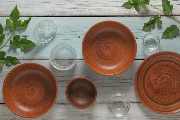 Глина и посуда на деревянный стол. квартира лежала. концепция кухни.