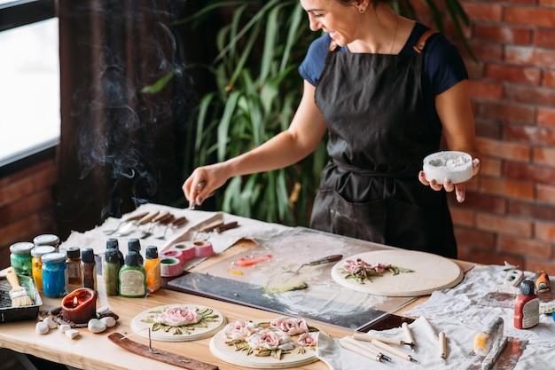 クレイアート。セラミッククラフト。クリエイティブなアーティストスタジオの雰囲気。職場でモデリングツールを持つ女性。お香の煙。