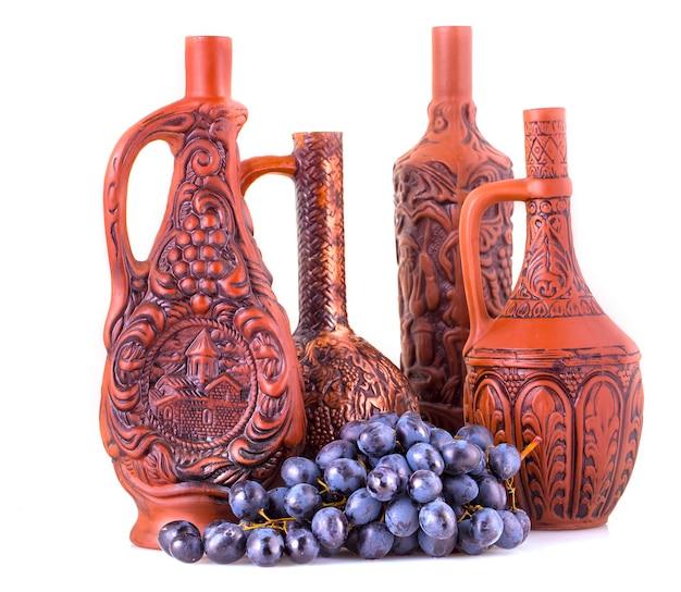 白い背景の上の粘土のボトルとブドウ。