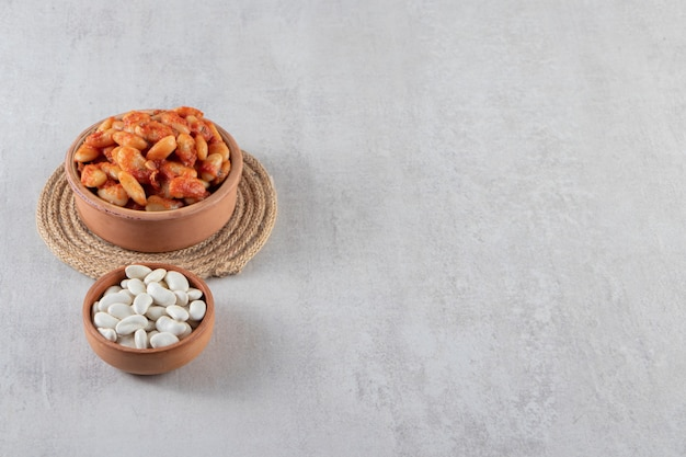 Clay bowl of boiled soy beans and raw beans on stone background.