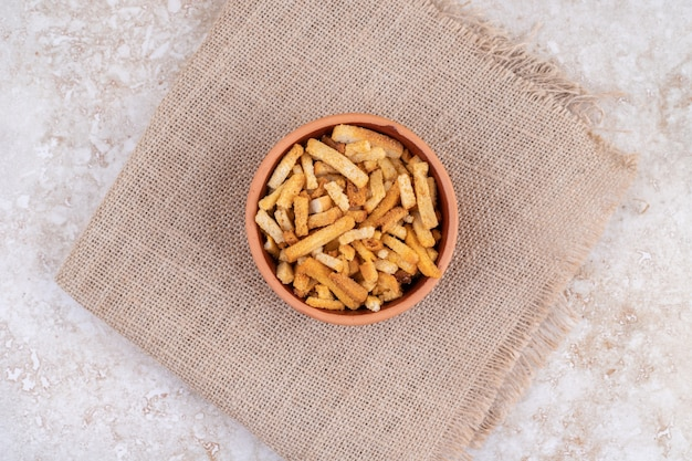 A clay bowl of breadsticks on a sackcloth