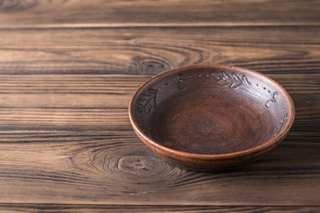 Clay bowl on a brown wooden table.