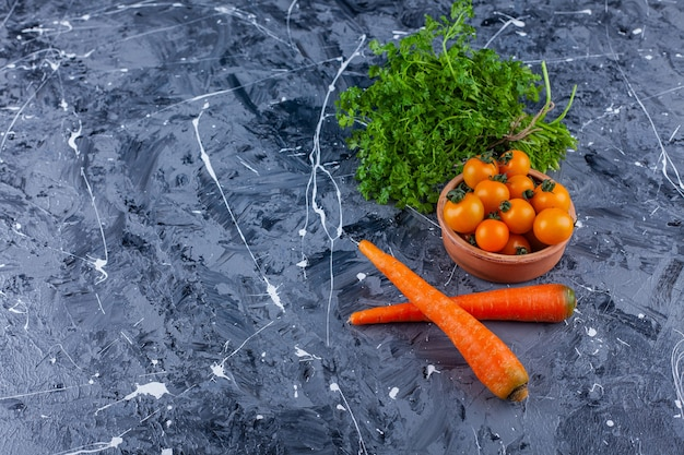 Clay bowl of cherry tomatoes with parsley leaves and carrots on blue.