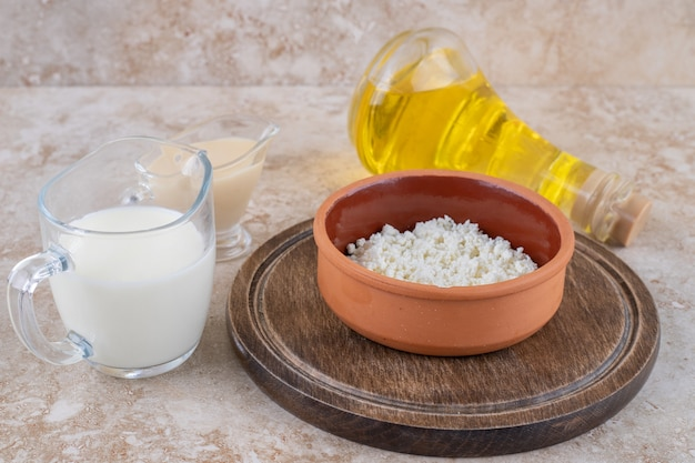 A clay bowl of cottage cheese with milk and a glass bottle of oil