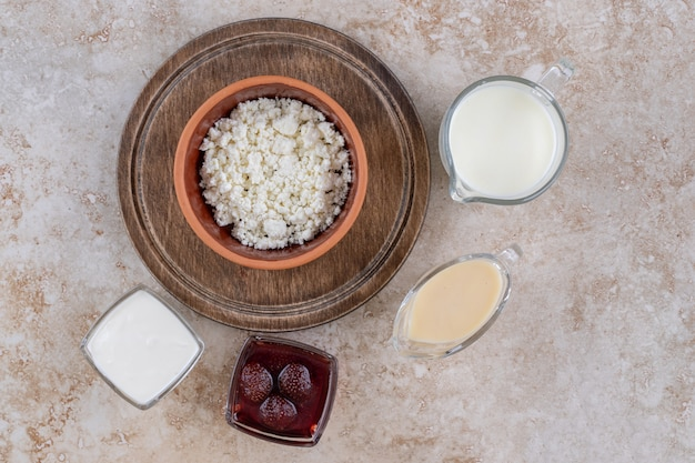 A clay bowl of cottage cheese with milk and strawberry jam