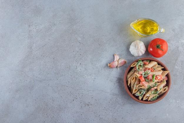 Ciotola di argilla di deliziose penne con verdure tritate e olio su fondo di pietra.