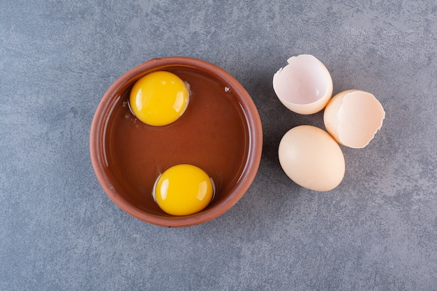 Clay bowl of egg yolk placed on stone table.