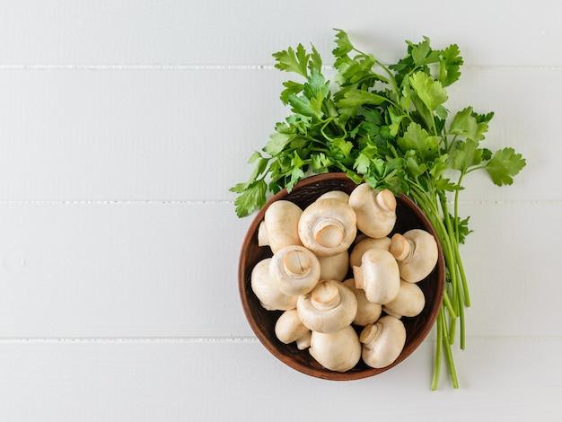 キノコと白いテーブルにパセリの大きな束で満たされた粘土ボウル。ベジタリアン料理。上からの眺め。フラット横たわっていた。