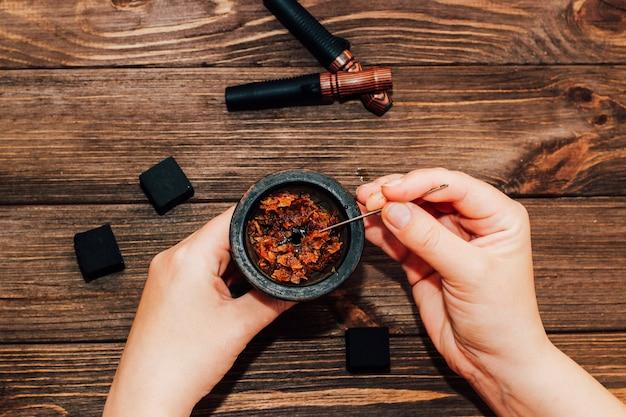 코코넛 석탄이 있는 물 담뱃대를 위한 점토 그릇, 나무 배경 위에 있는 나무 마우스피스. 소녀는 흡연 담배를 채웁니다.