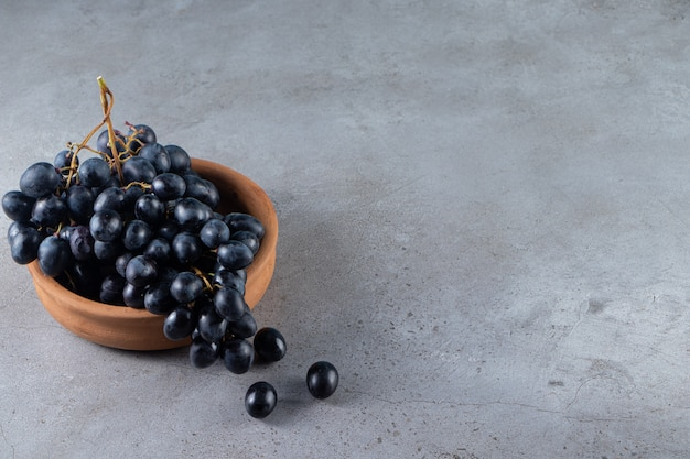 Clay bowl of fresh black grapes on stone table.