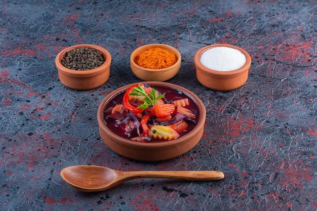Ciotola di argilla di zuppa di verdure fresche con condimenti sulla superficie in marmo
