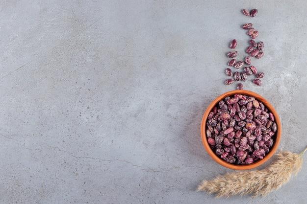 石の背景に生豆でいっぱいの粘土ボウル。