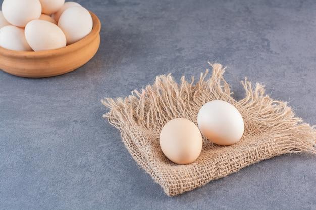 돌 테이블에 원시 유기농 계란의 전체 클레이 그릇.