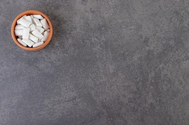 돌 테이블 위에 놓인 흰색 껌으로 가득 찬 점토 그릇.