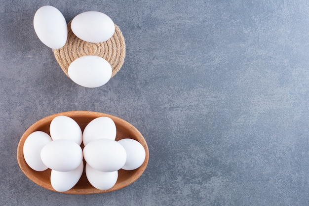 Clay bowl full of raw white eggs on stone table.
