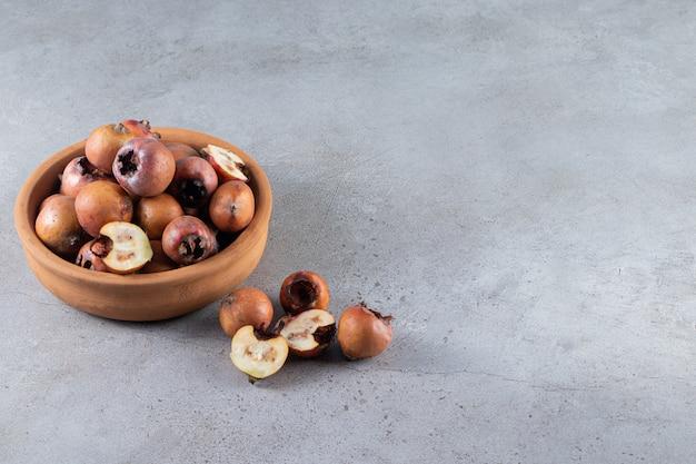 Ciotola di argilla piena di frutti maturi nespola su sfondo di pietra.