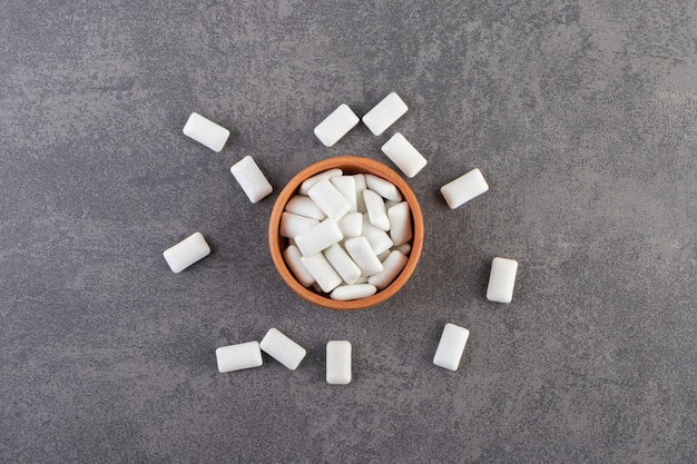 Clay bowl full of white chewing gums placed on a stone table .