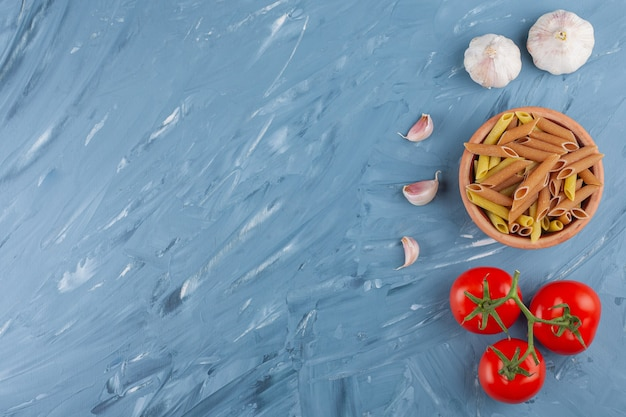 A clay bowl of multi colored raw pasta with garlics and fresh red tomatoes on a blue table.