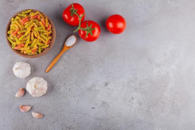 Una ciotola di argilla di pasta a spirale cruda multicolore con aglio e pomodori rossi freschi.