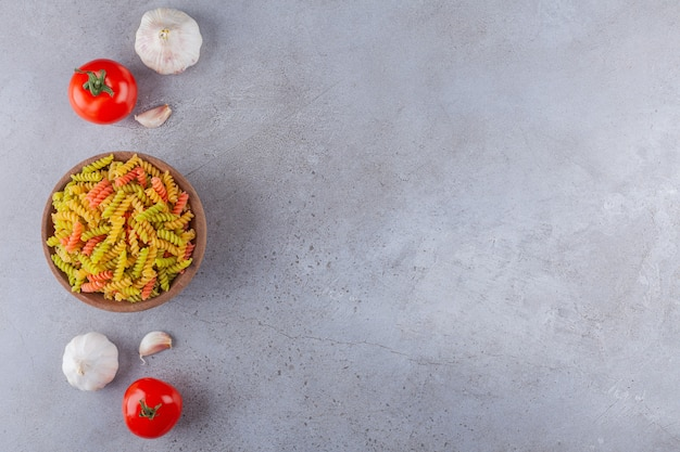 A clay bowl of multi colored raw spiral pasta with garlic and fresh red tomatoes.