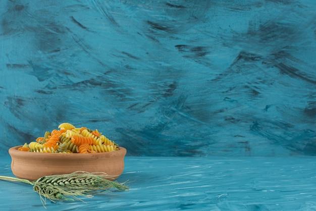 青い背景にカラフルな生フジッリパスタの粘土ボウル。