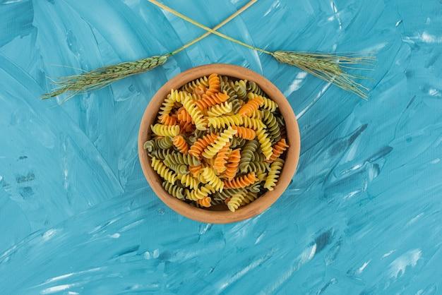 파란색 표면에 다채로운 원시 fusilli 파스타의 점토 그릇