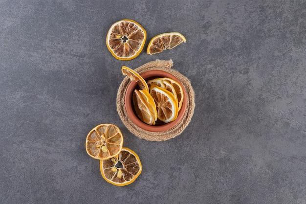 Глиняная чаша сушеных нарезанных лимонов на каменном фоне.