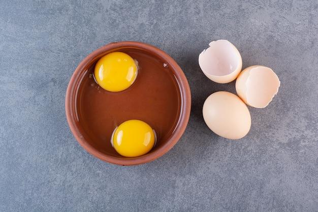 계란 노른자의 점토 그릇은 돌 테이블에 배치됩니다.