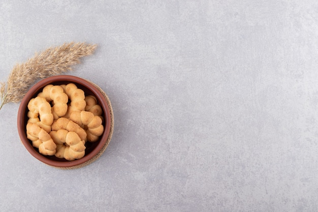 Глиняная чаша сладкого печенья в форме цветка на каменном столе.