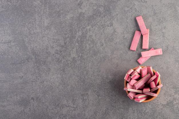 돌 테이블에 긴 분홍색 쫄깃한 스틱의 점토 그릇.