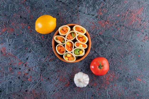 Глиняная миска макарон, фаршированная нарезанными овощами на мраморной поверхности. Premium Фотографии