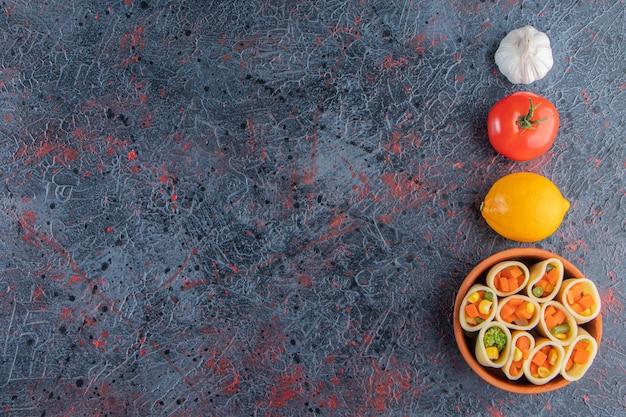 Глиняная миска макарон, фаршированная нарезанными овощами на мраморной поверхности.