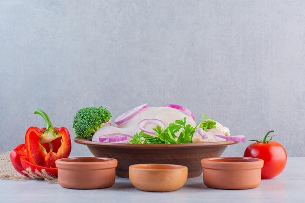 石の表面にさまざまな調味料が入った生の丸ごと鶏肉の粘土ボウル。
