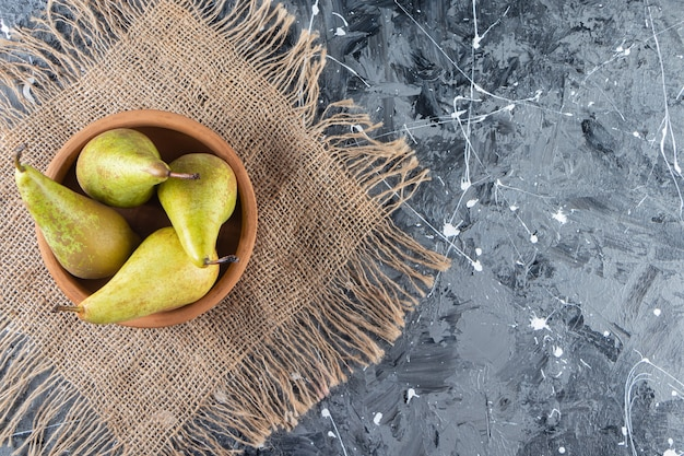 大理石の背景に熟した緑梨の粘土ボウル。