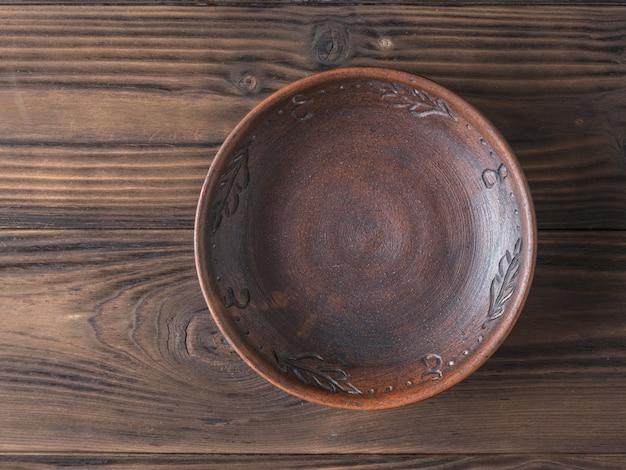 Глиняная чаша на коричневом деревянном столе. вид сверху. керамика для кухни. плоская планировка.
