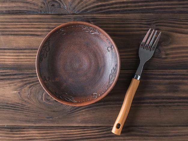 茶色の木製テーブルの上の粘土ボウル。
