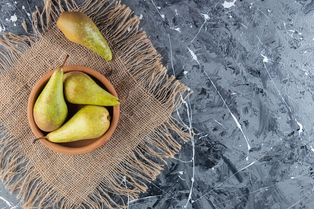 Clay bowl of ripe green pears on marble background.